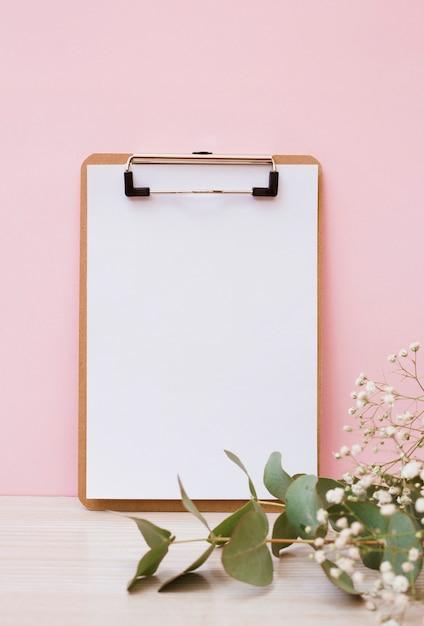 Leeres weißbuch auf klemmbrett mit blättern und babyatem blüht auf hölzernem schreibtisch gegen rosa hintergrund Kostenlose Fotos