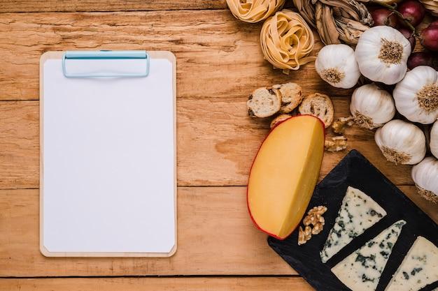 Leeres weißbuch auf klemmbrett nahe gesunden bestandteilen auf schreibtisch Kostenlose Fotos