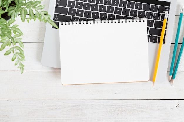 Leeres weißes notizbuch auf laptop-computer auf hölzerner tabelle Premium Fotos