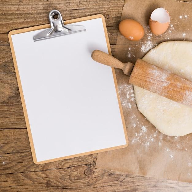 Leeres weißes papier in der zwischenablage; flacher teig und eierschalen auf pergamentpapier über dem holztisch Kostenlose Fotos