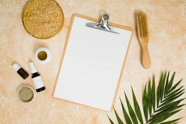Leeres weißes papier in der zwischenablage, umgeben von rhassoul-ton; salz; honig; essentielle öle; pinsel und palmblätter Kostenlose Fotos