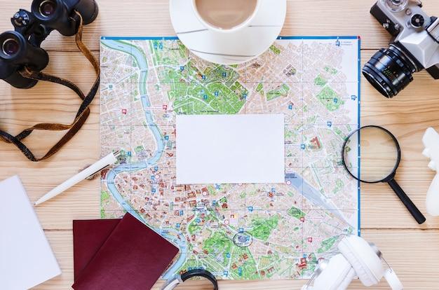 Leeres weißes papier; teetasse und verschiedene reisende zubehör auf hölzernen hintergrund Kostenlose Fotos