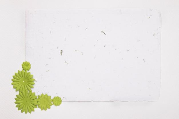 Leeres weißes strukturiertes papier verziert mit grünen blumen gegen hintergrund Kostenlose Fotos