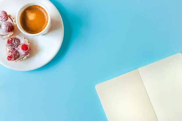 Leerseite und törtchen mit kaffeeglas auf blauem hintergrund Kostenlose Fotos