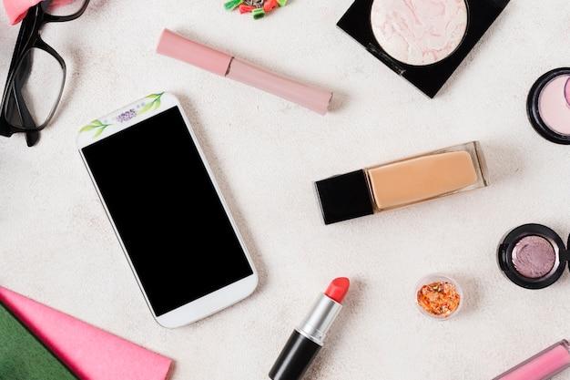 Legen sie make-up-produkte und smartphone aus Kostenlose Fotos