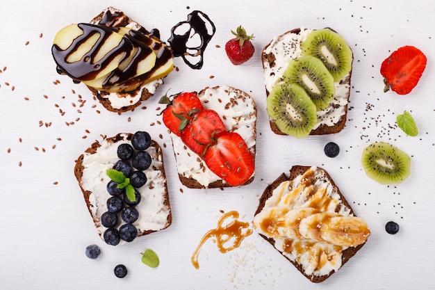 Legen sie süße sandwiches mit frischkäse und frischen beeren und obst über Premium Fotos