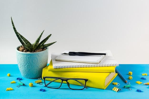Lehrbücher für brillen; holzbuchstaben und ein sukkulententopf auf dem tisch; auf dem hintergrund eines blauen papiers. das konzept des lehrertages. kopieren sie platz. Premium Fotos