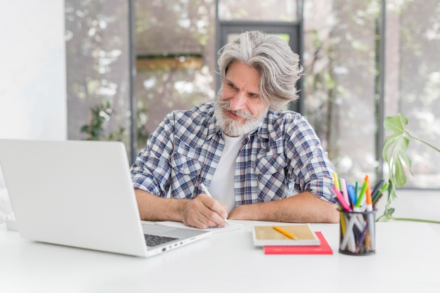 Lehrer, der am schreibtisch bleibt, der auf notizbuch schreibt und laptop betrachtet Premium Fotos