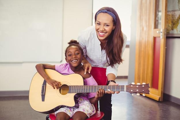 Lehrer, der einem mädchen hilft, eine gitarre im klassenzimmer zu spielen Premium Fotos
