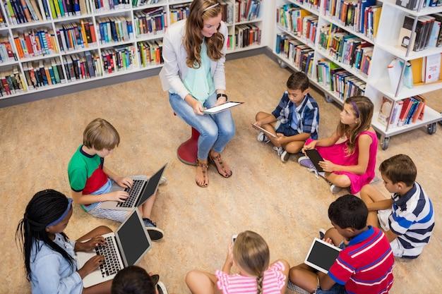 Lehrer, der ihren kursteilnehmern mit computern lektion gibt Premium Fotos