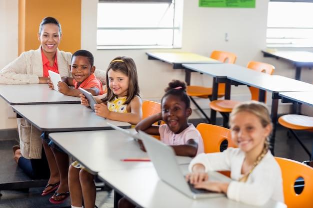 Lehrer, der ihren kursteilnehmern mit laptopen lektion gibt Premium Fotos