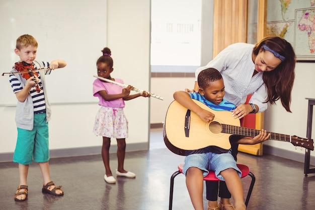 Lehrer, der kindern hilft, ein musikinstrument im klassenzimmer zu spielen Premium Fotos