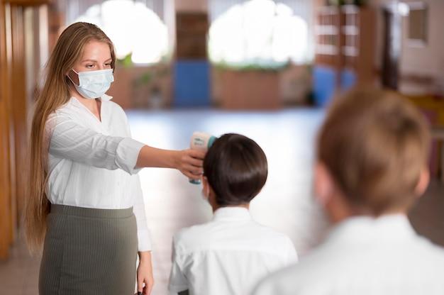 Lehrer, der körpertemperatur in der schule nimmt Kostenlose Fotos