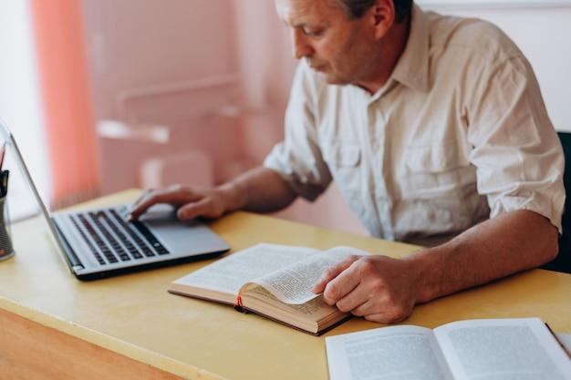 Lehrer, der mit offenem lehrbuch und laptop und arbeiten sitzt. Premium Fotos