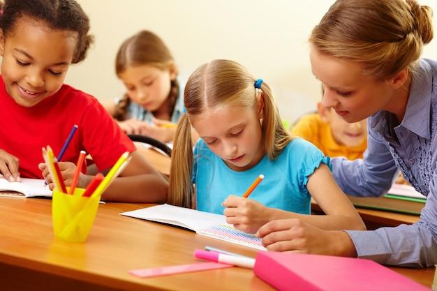 Lehrer helfen student mit schriftlichen arbeiten Kostenlose Fotos