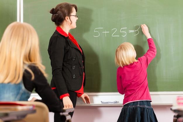 Lehrer mit schüler im schulunterricht Premium Fotos