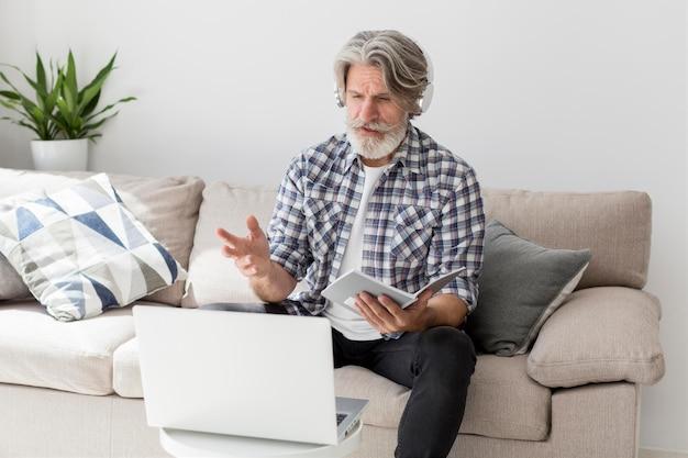 Lehrer spricht am laptop, der notizbuch hält Kostenlose Fotos