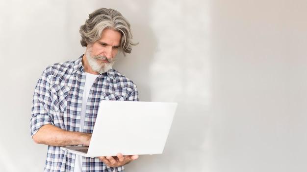 Lehrer stehend und hält laptop Kostenlose Fotos