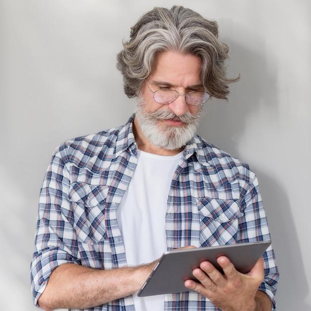 Lehrer stehend und hält tablette Kostenlose Fotos