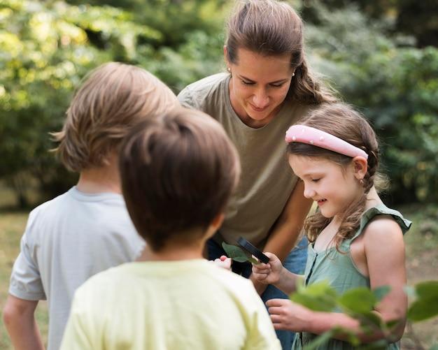 Lehrer und kinder, die blätter betrachten Kostenlose Fotos