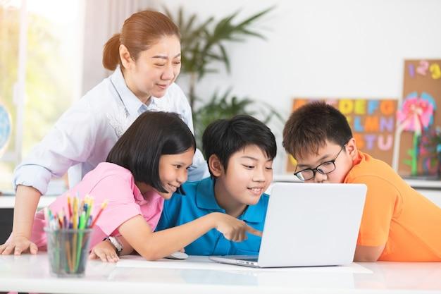 Lehrer und nette asiatische kinder, die zusammen laptop-computer verwenden. Premium Fotos