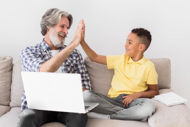 Lehrer und schüler high fiving auf der couch Kostenlose Fotos