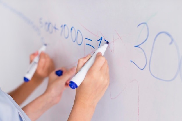 Lehrer und schüler machen kalkül auf einem whiteboard Kostenlose Fotos