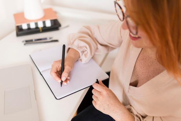 Lehrerin am schreibtisch schreibt in der tagesordnung während des online-unterrichts Kostenlose Fotos