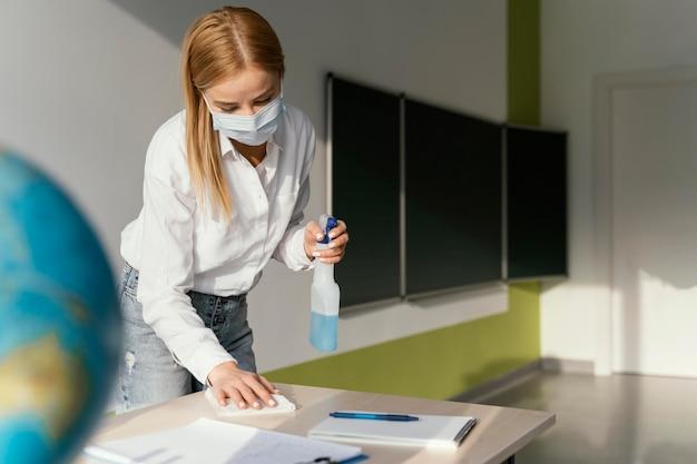 Lehrerin desinfiziert ihren schreibtisch im klassenzimmer Kostenlose Fotos
