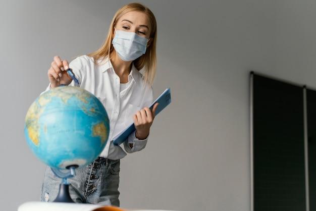 Lehrerin im klassenzimmer mit zwischenablage, die auf globus zeigt Kostenlose Fotos