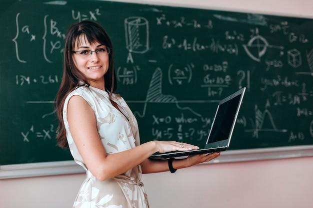 Lehrerin in den gläsern, die offenen laptop halten und die kamera betrachten. Premium Fotos