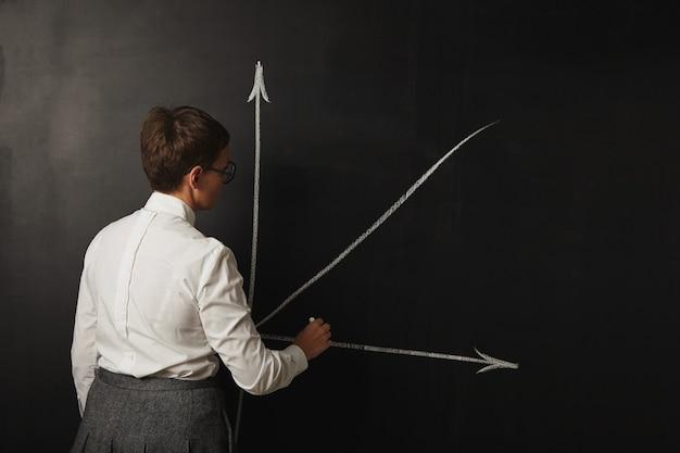Lehrerin mit kurzen haaren in der weißen bluse und im grauen rock, die eine grafik auf tafel zeichnen Kostenlose Fotos