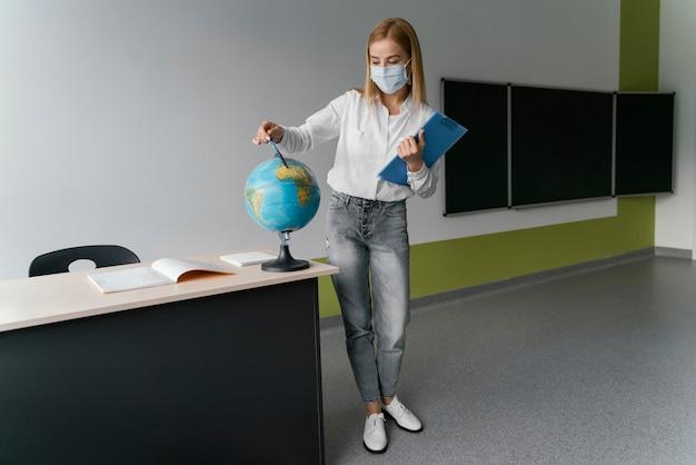 Lehrerin mit zwischenablage, die auf globus im klassenzimmer zeigt Kostenlose Fotos