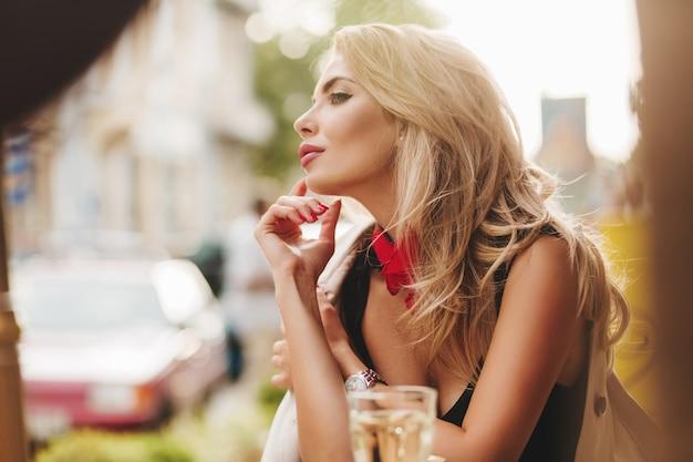 Leicht gebräunte frau mit rosa lippenstift, der weg schaut, während im morgen im lieblingscafé gekühlt wird Kostenlose Fotos