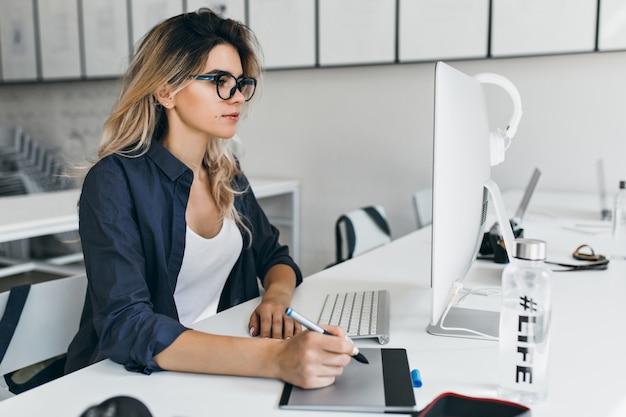 Leicht gebräuntes mädchen in der brille und im schwarzen hemd, die mit computer im gemütlichen büro arbeiten Kostenlose Fotos