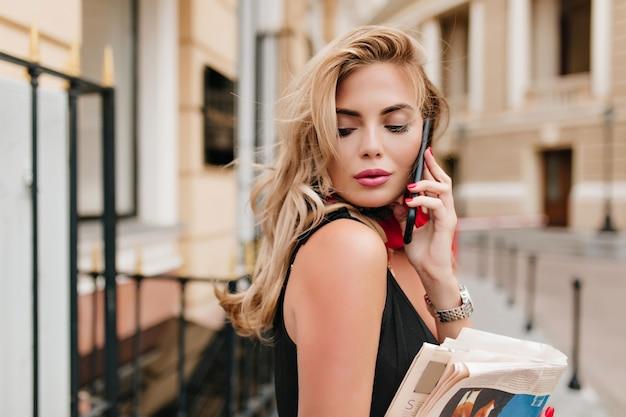 Leicht gebräuntes weibliches model mit langen blonden haaren, das jemandem am telefon mit geschlossenen augen zuhört Kostenlose Fotos