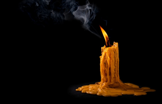 Leichte flammenkerze, die hell auf schwarz brennt Premium Fotos