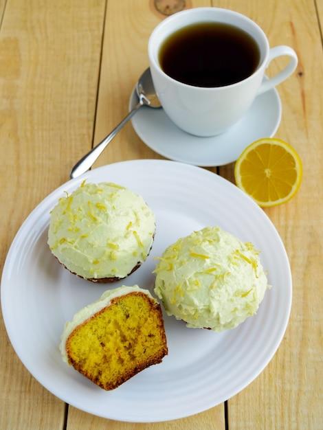 Leichte zitronen-cupcakes-muffins auf hölzernem hintergrund und eine tasse tee. Premium Fotos