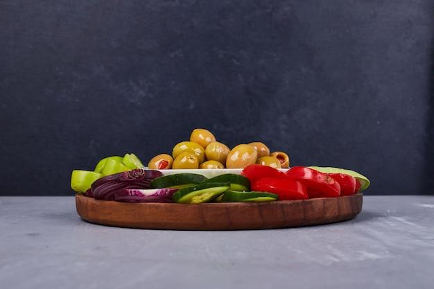 Leichter salat mit gemüse und kräutern in holzplatte. Kostenlose Fotos