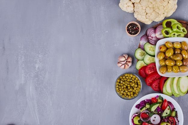 Leichter salat mit gemüse und kräutern in weißen tellern. Kostenlose Fotos