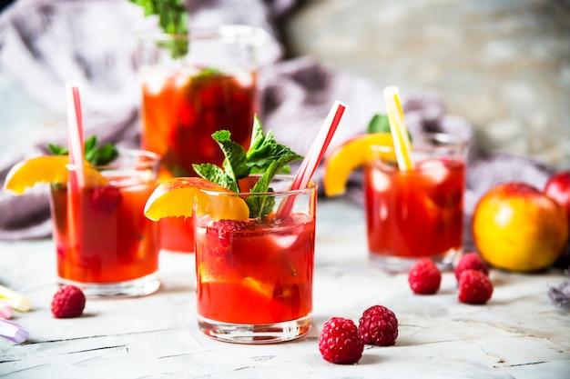 Leichtes sommererfrischungsgetränk mit früchten und beeren - sangria. in gläsern auf einem grauen tisch Premium Fotos