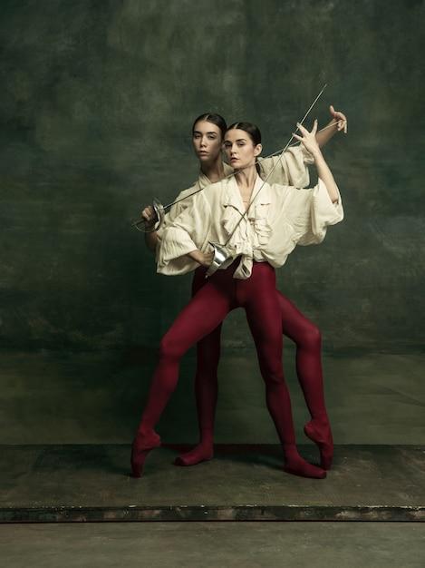 Leidenschaftlich. zwei junge balletttänzerinnen mögen duellanten mit schwertern an dunkelgrüner wand. kaukasische modelle tanzen zusammen. ballett und zeitgenössisches choreografiekonzept. Kostenlose Fotos