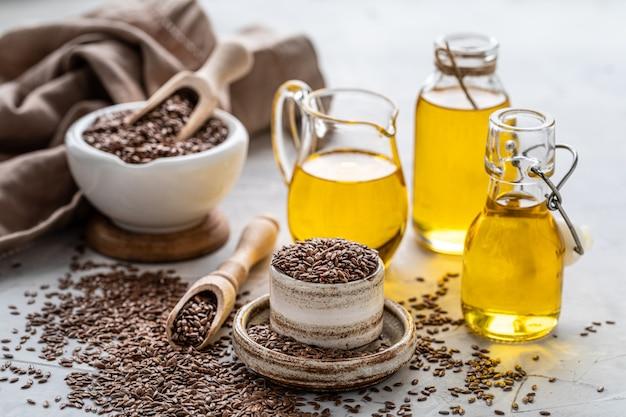 Leinsamenöl in einer flasche und einer keramikschale mit braunen leinsamen und holzlöffel Premium Fotos