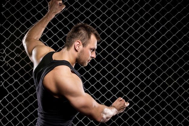 Leistungsfähiger kerl, der seine muskeln auf zaun zeigt Kostenlose Fotos