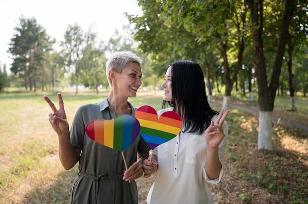 Lesbenpaar, das lgbt herzformfahne hält Kostenlose Fotos