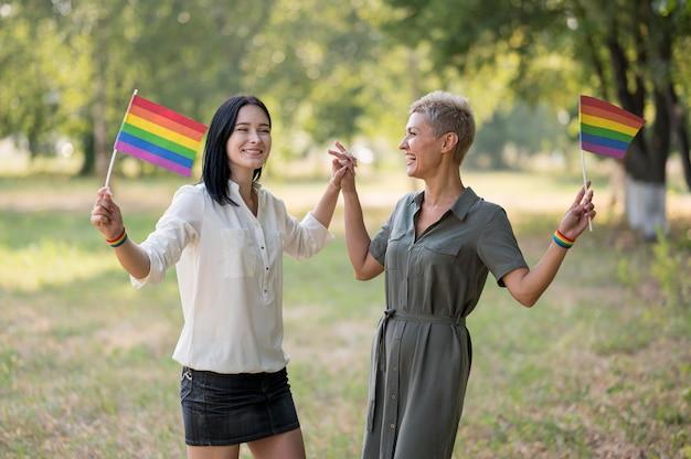 Lesbenpaar im park mit flaggen Kostenlose Fotos
