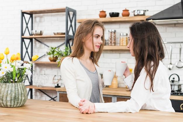 Lesbische junge paare, die zu hause einander trinkenden kaffee der hand halten Kostenlose Fotos