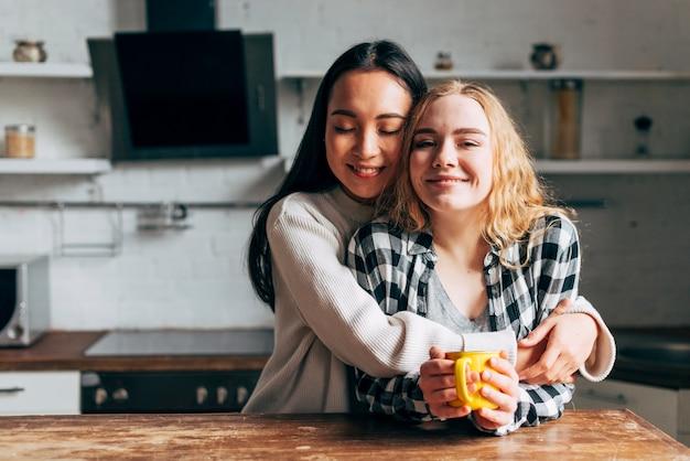 Lesbische umarmende paare beim trinken des tees auf küche Kostenlose Fotos