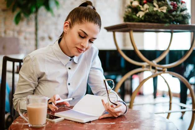 Lesung der jungen frau im café. Premium Fotos