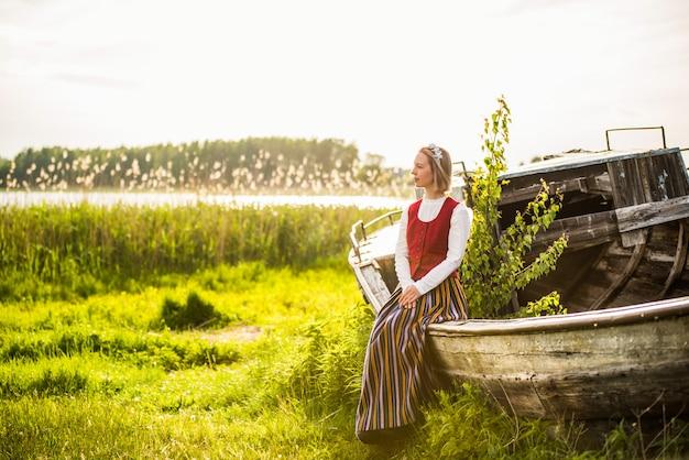 Lettische frau in traditioneller kleidung auf altem boot. Premium Fotos